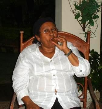 Dominikanische Frau mit Zigarre im Schaukelstuhl