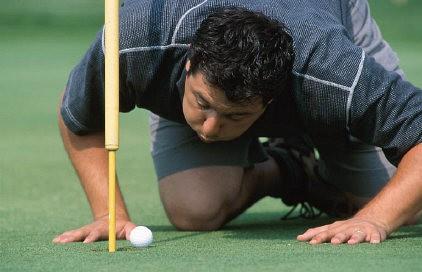 Golfspieler bläst den Golfball ins Loch