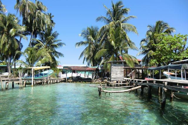 Ein Dorf am Meer mit Anlegestelle und Palmen